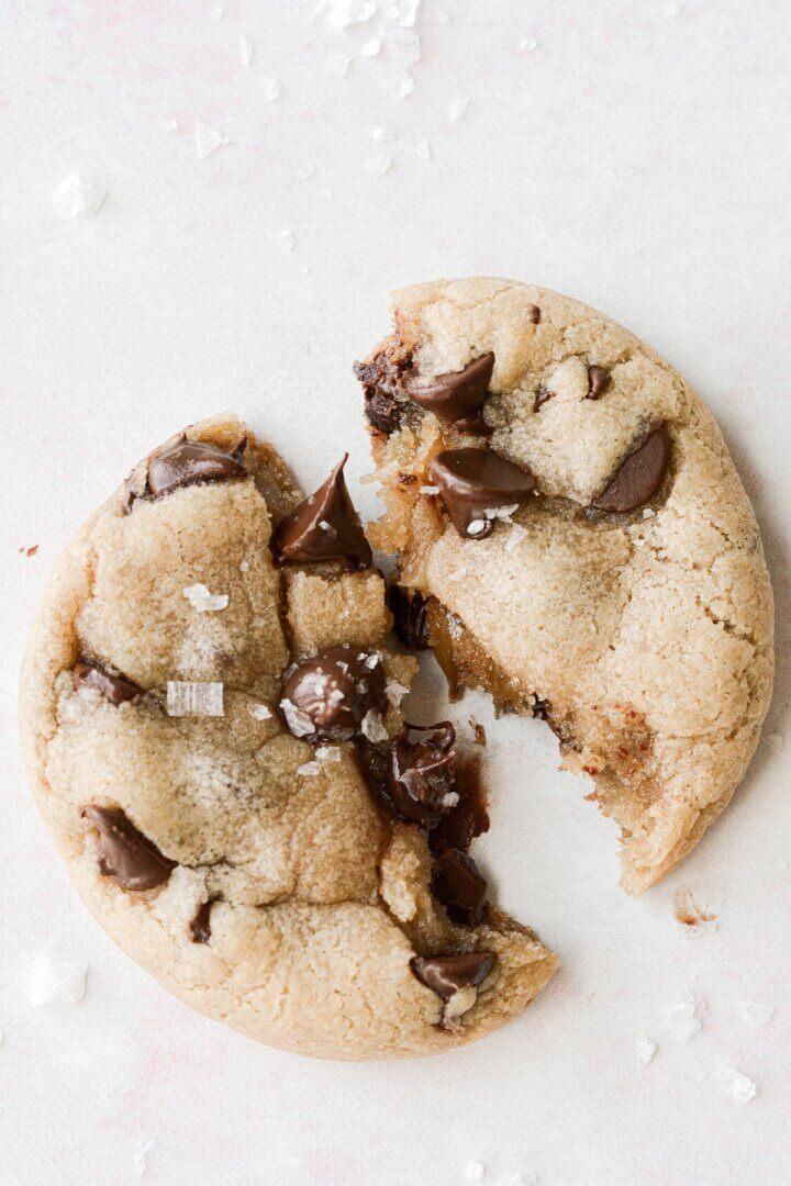 A caramel stuffed chocolate chip cookie broken in half.