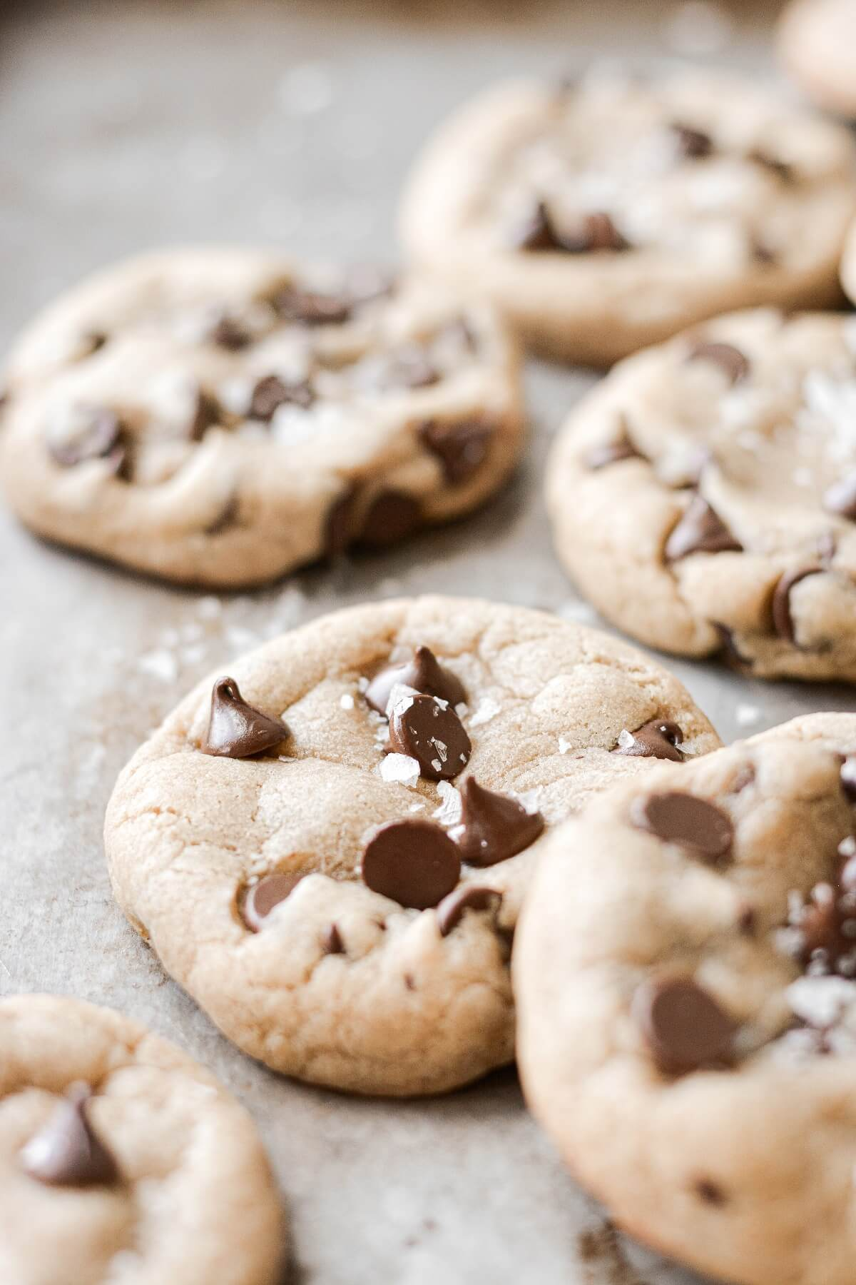 Caramel stuffed chocolate chip cookies sprinkled with flaky salt on a baking sheet.