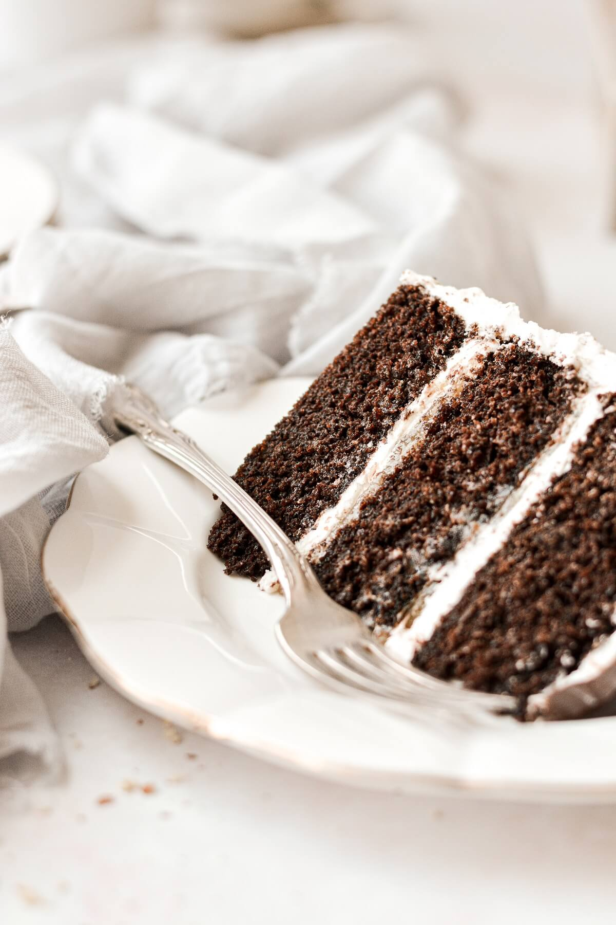 A slice of chocolate almond cake on a white plate.