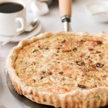 Baked quiche Lorraine next to a cup of coffee.