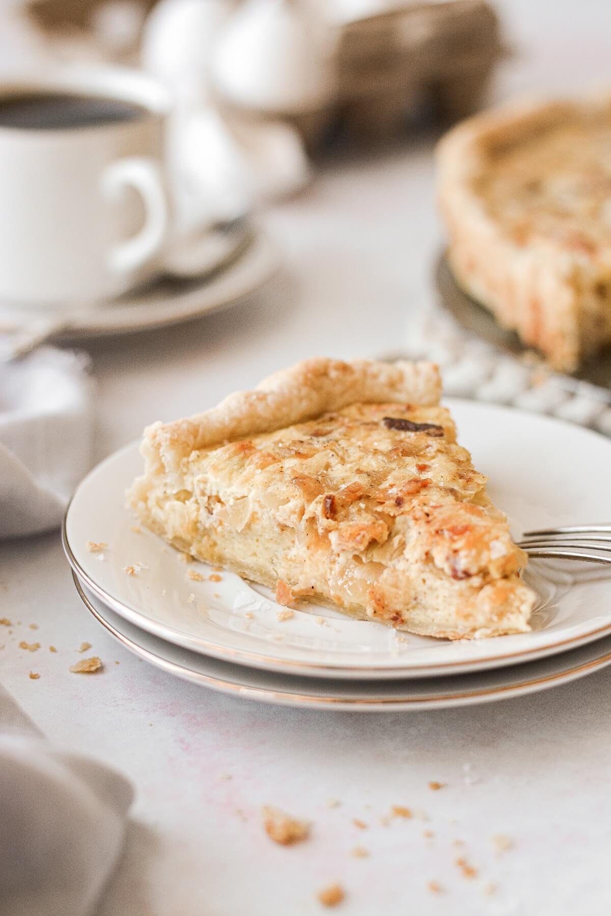 A slice of quiche Lorraine on a white plate.