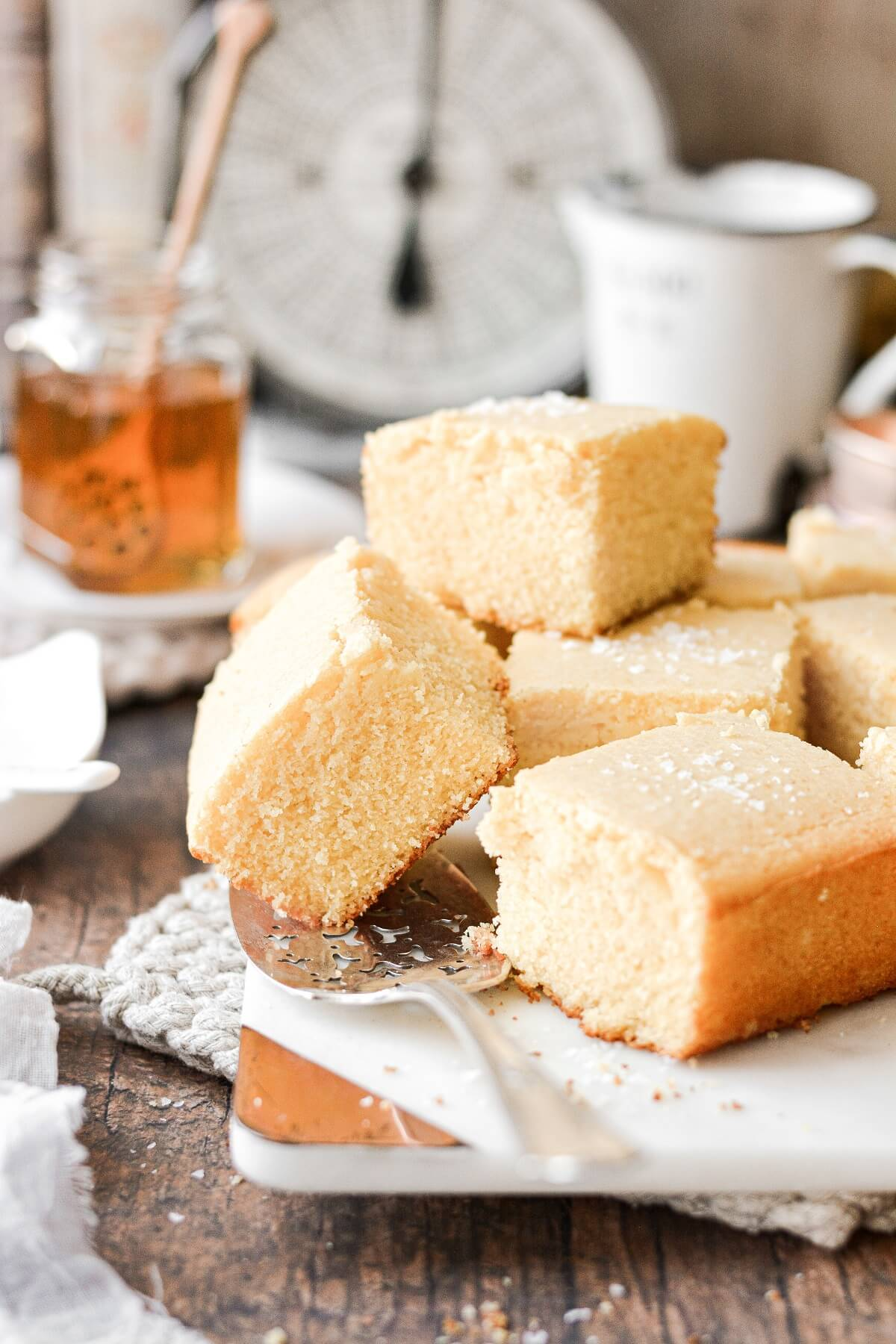 Squares of cornbread stacked on a marble serving board.
