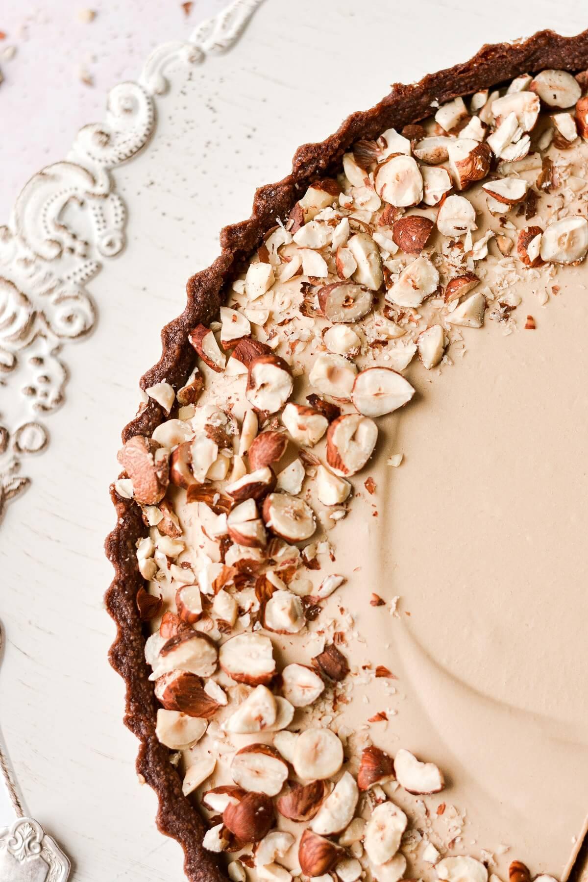 Closeup of coffee cream tart topped with hazelnuts.