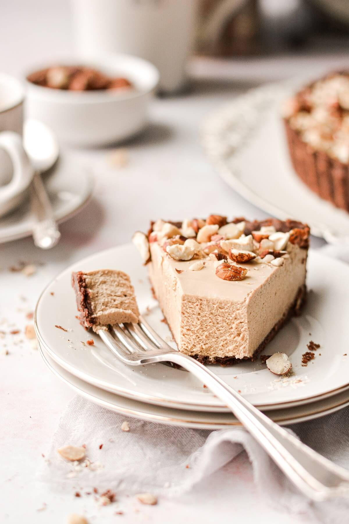 A slice of coffee cream tart with a bite taken.
