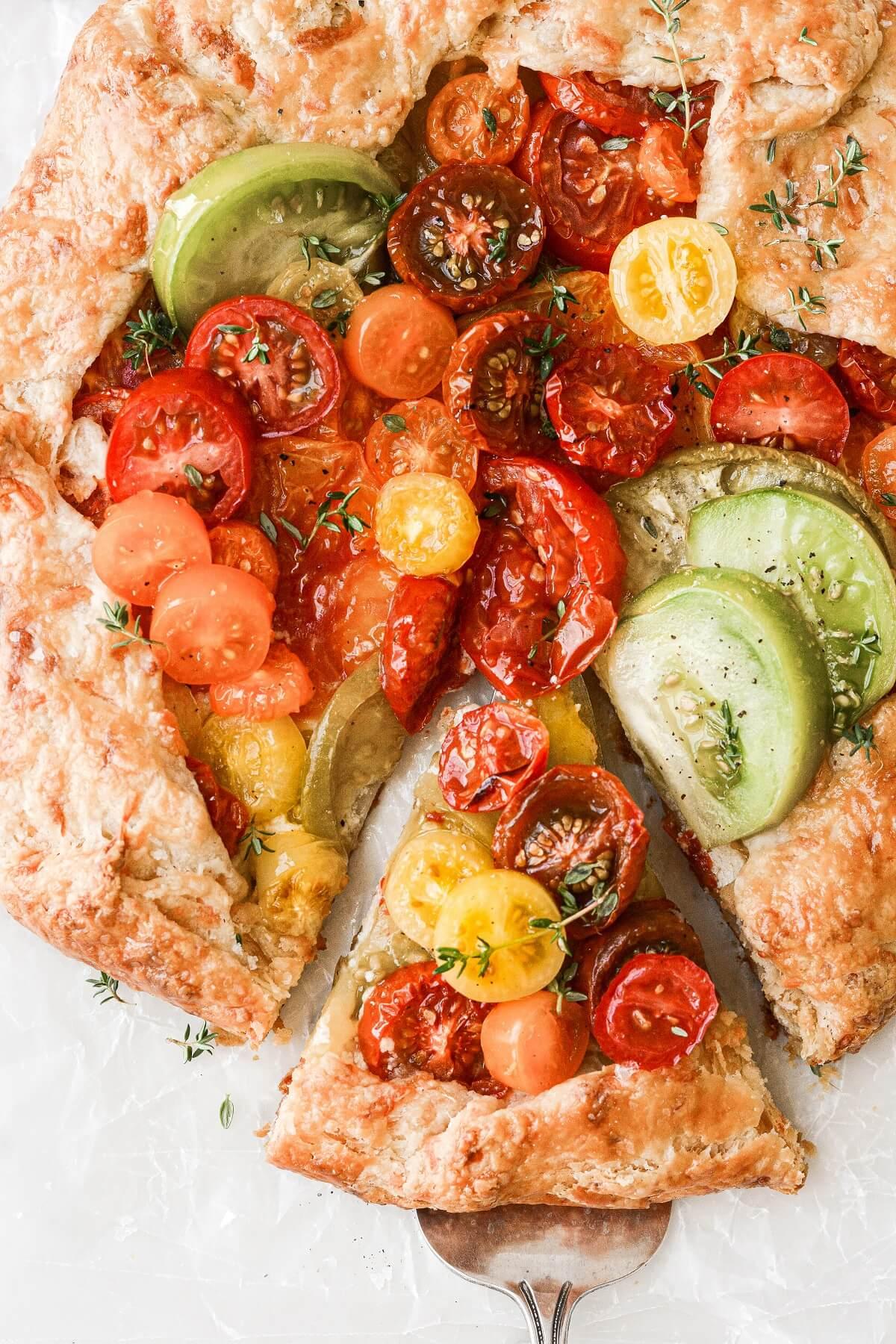 A slice of tomato galette on a pie server.