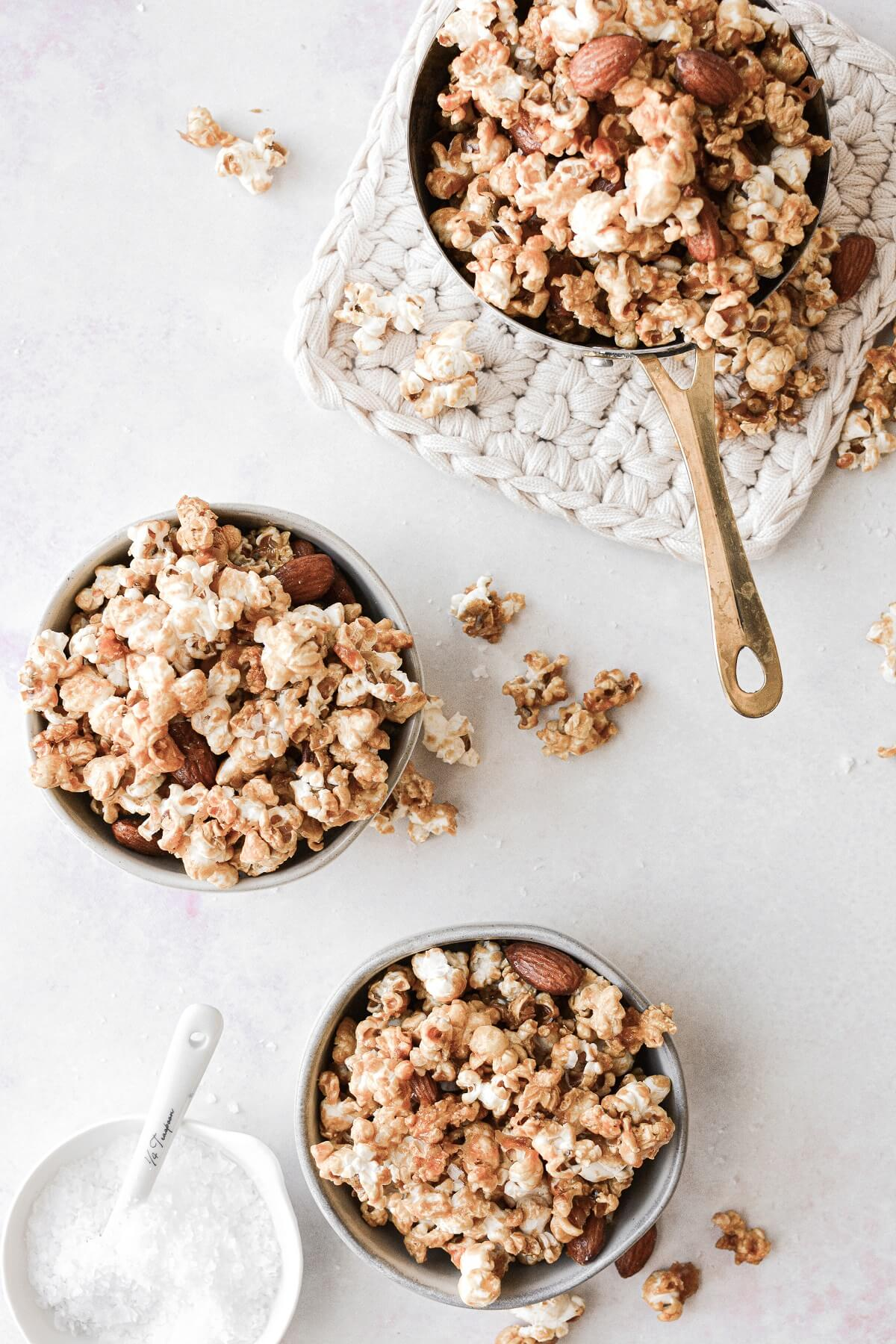 Bowls of homemade caramel popcorn with almonds.
