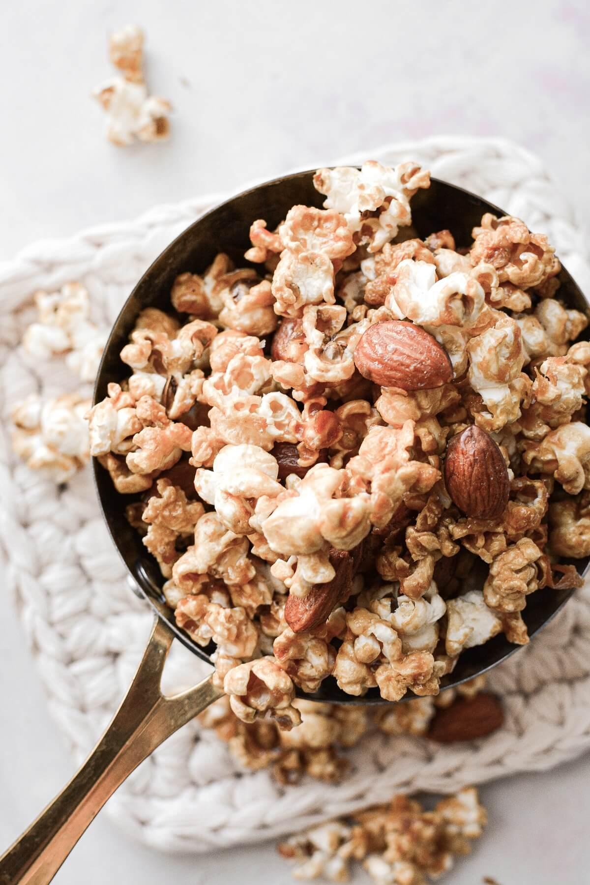 Homemade caramel popcorn and almonds in a saucepan.