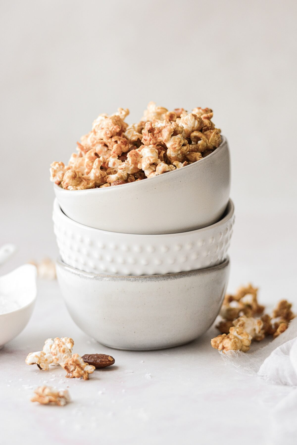A stack of bowls with the top one filled with caramel popcorn.