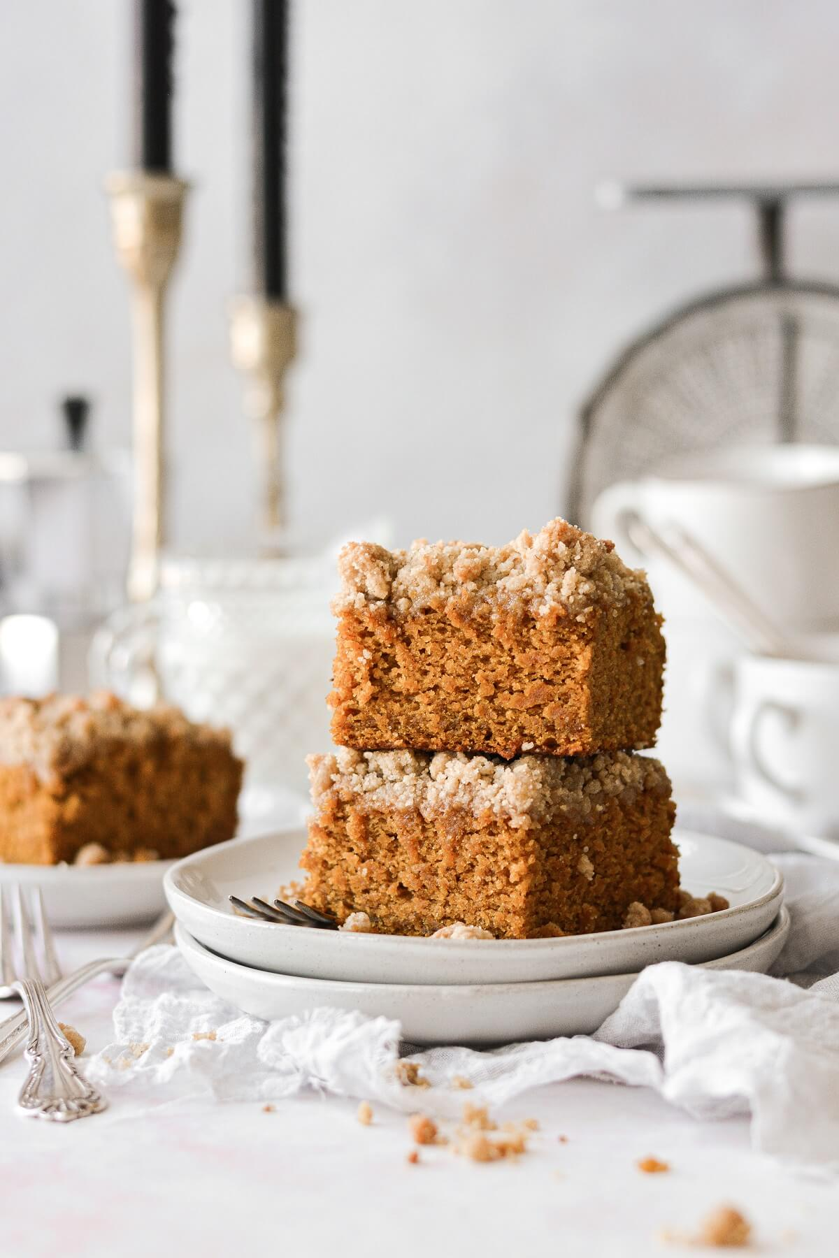 Pieces of pumpkin crumb coffee cake stacked on white plates.