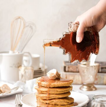Maple syrup being poured on top of a stack of pumpkin pancakes.