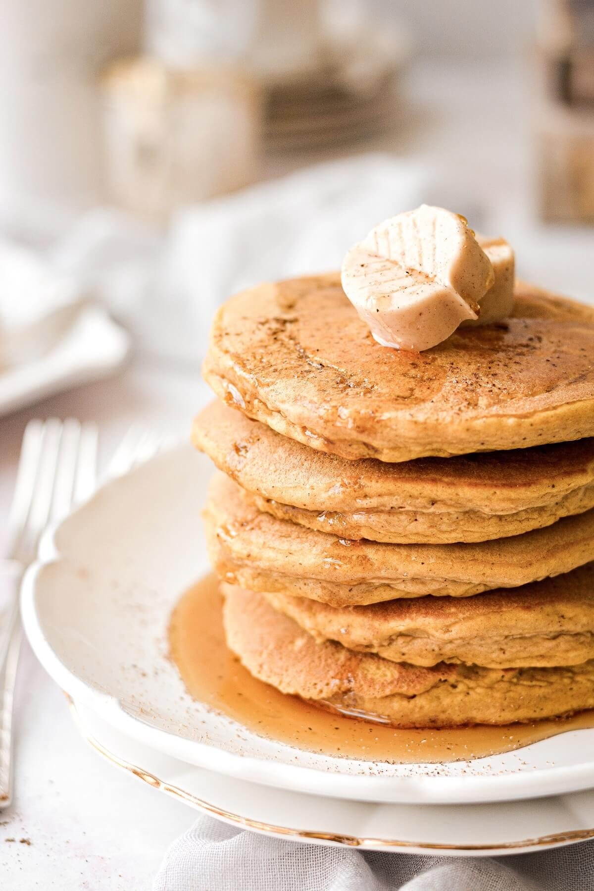 A stack of pumpkin pancakes topped with a butter leaf.