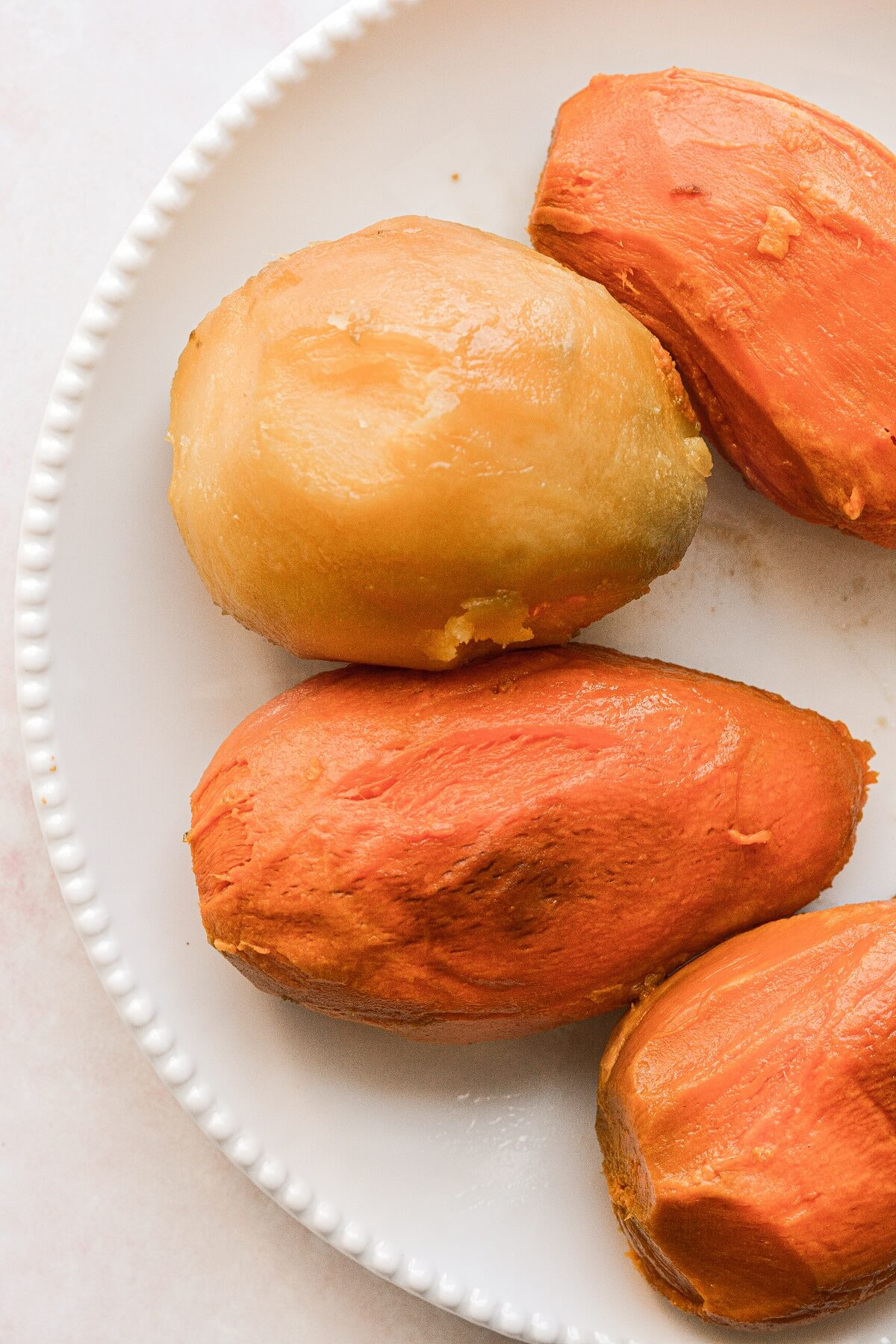 Roasted sweet potatoes without their peel, on a white plate.