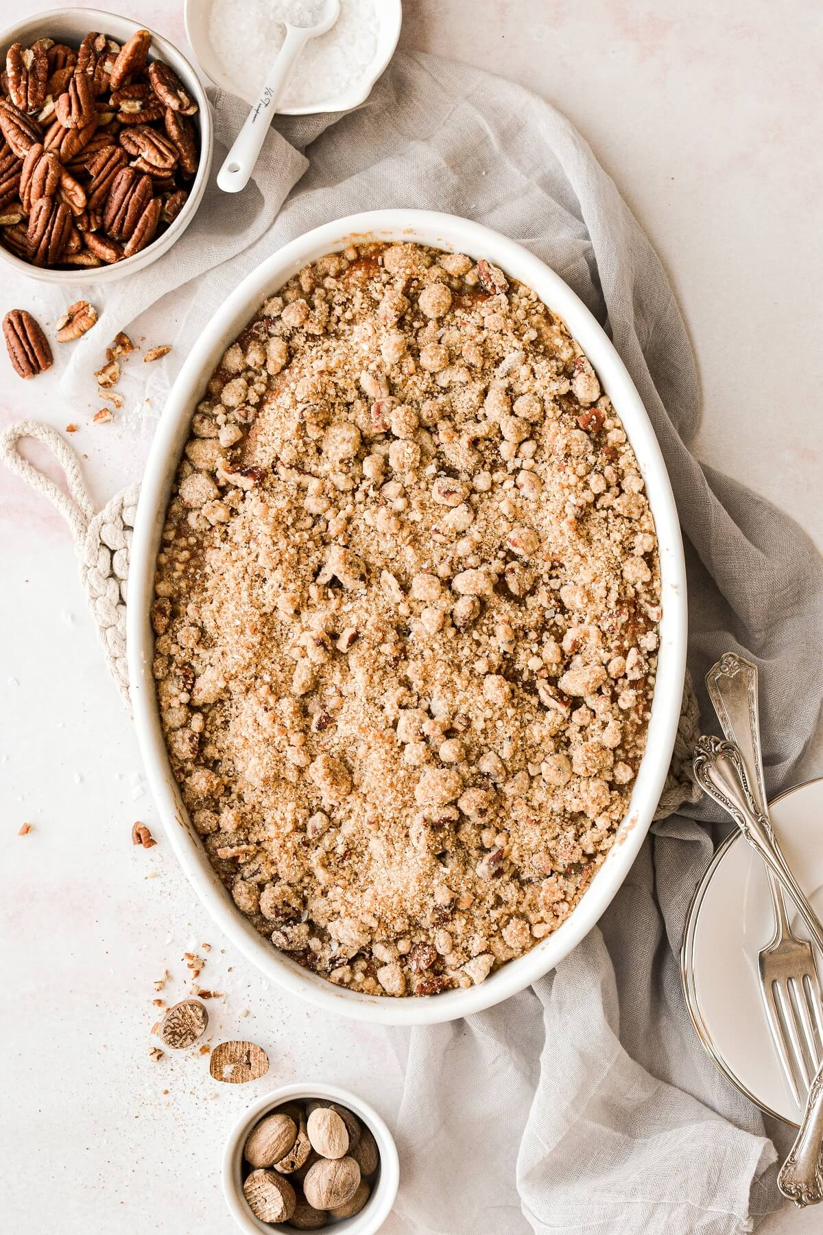 Sweet potato casserole with brown sugar pecan streusel crumb topping, baked in an oval baking dish.