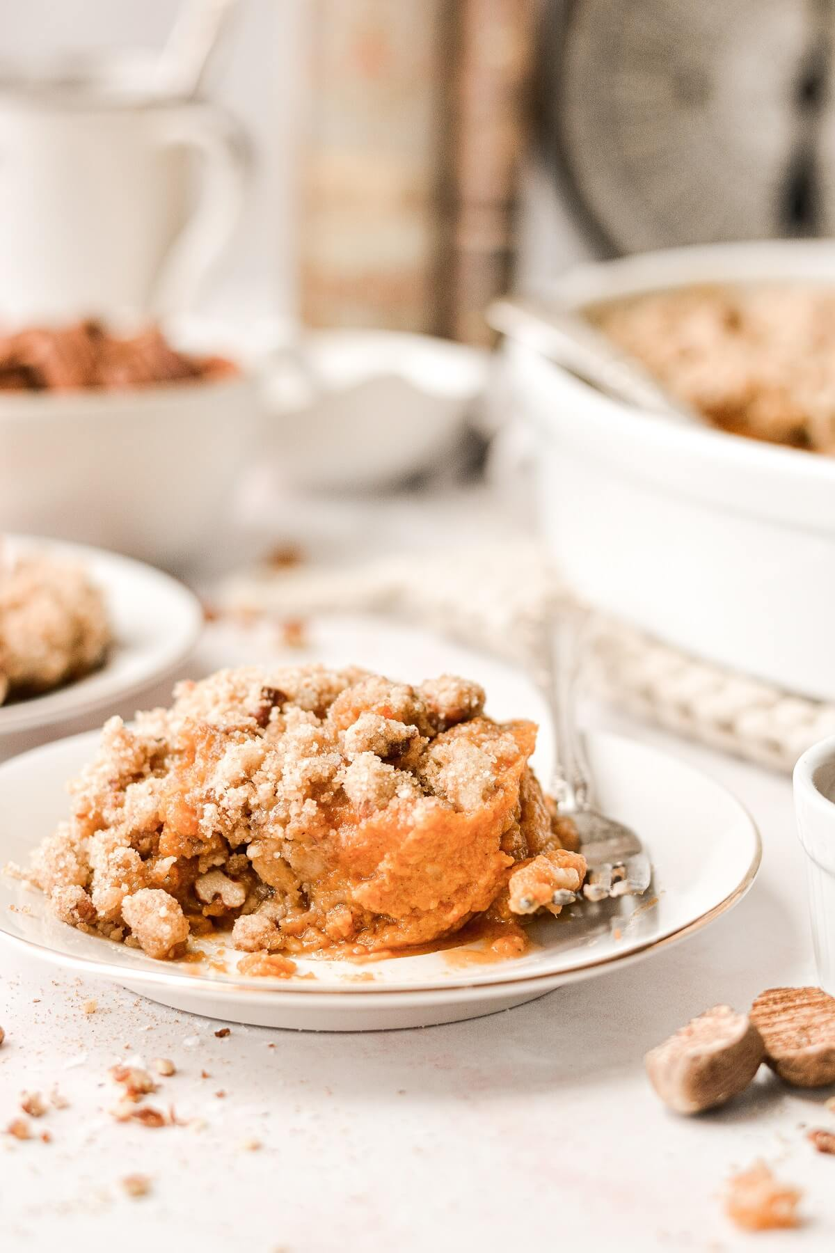 A scoop of sweet potato casserole with crumb topping on a white plate.