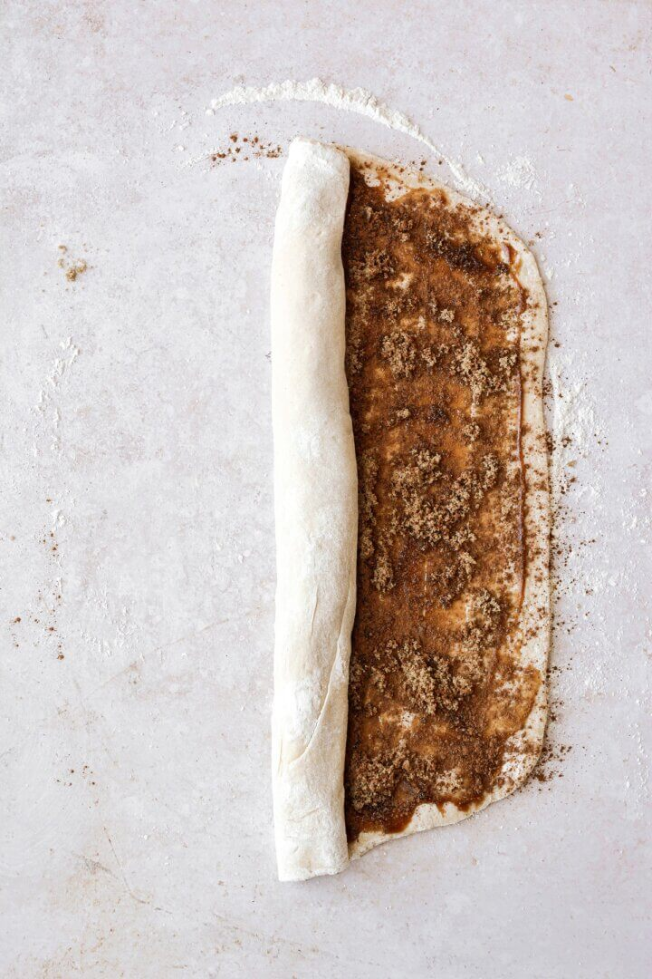 Dough being rolled up into a log.