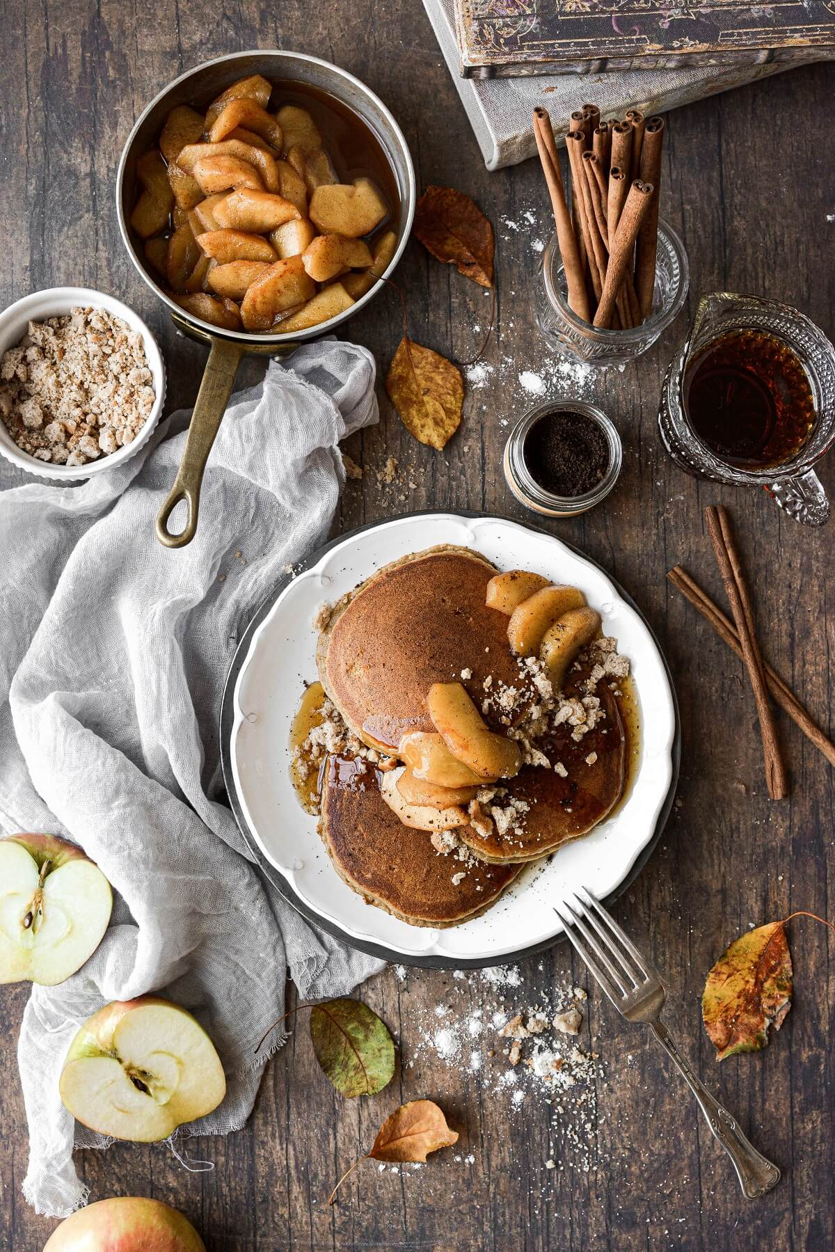Apple cider pancakes on a plate, surrounded by apples, syrup and cinnamon sticks.