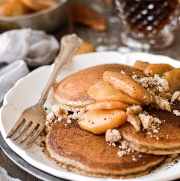 Apple cider pancakes with cinnamon apples, syrup, and cookie crumbles.