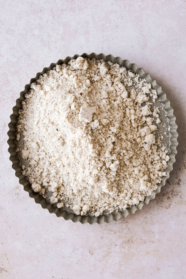 Shortbread dough crumbs piled into a round fluted tart pan.