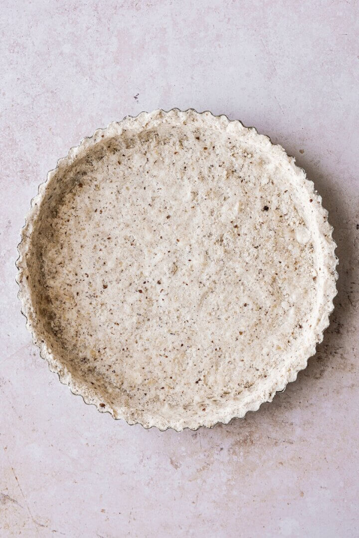 Shortbread dough pressed into a round fluted tart pan.