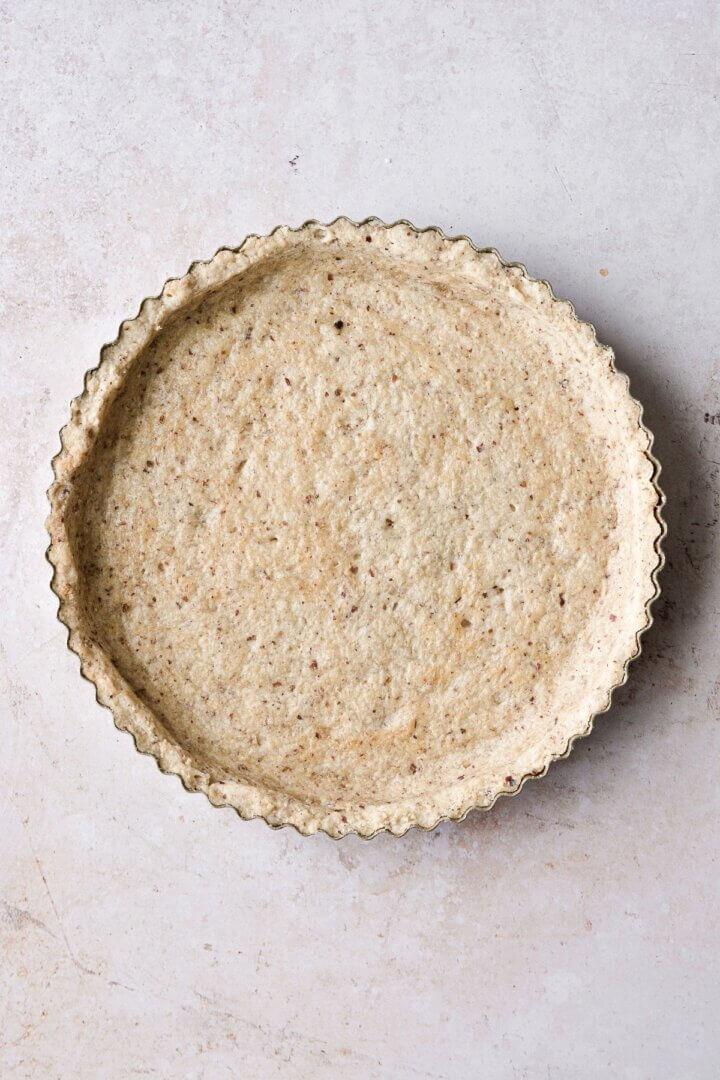 A baked pecan shortbread crust in a tart pan.