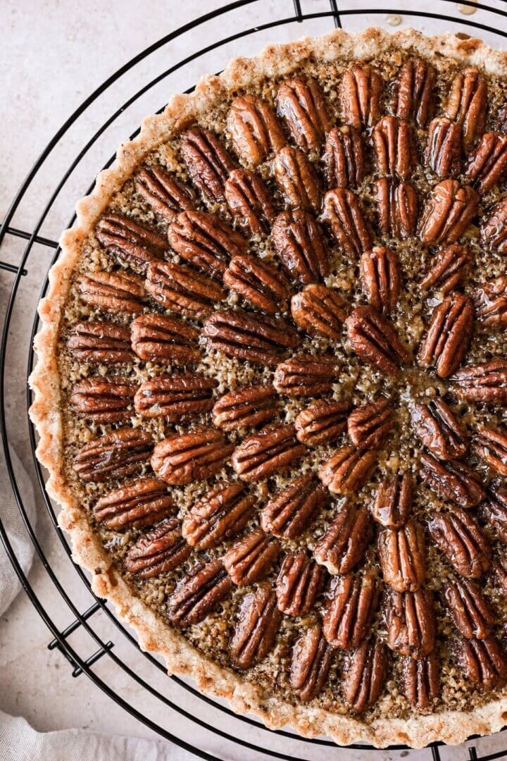 Closeup of a maple pecan tart decorated with pecans.