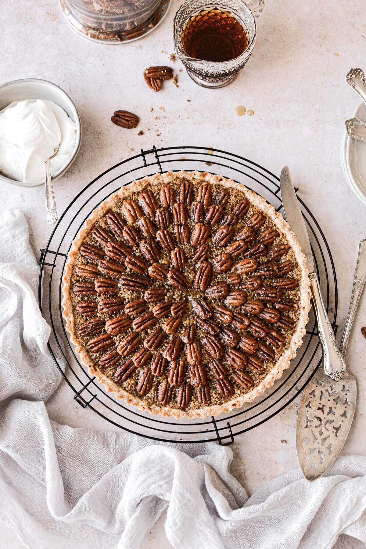 A maple pecan tart decorated with pecans, next to a bowl of whipped cream and maple syrup.
