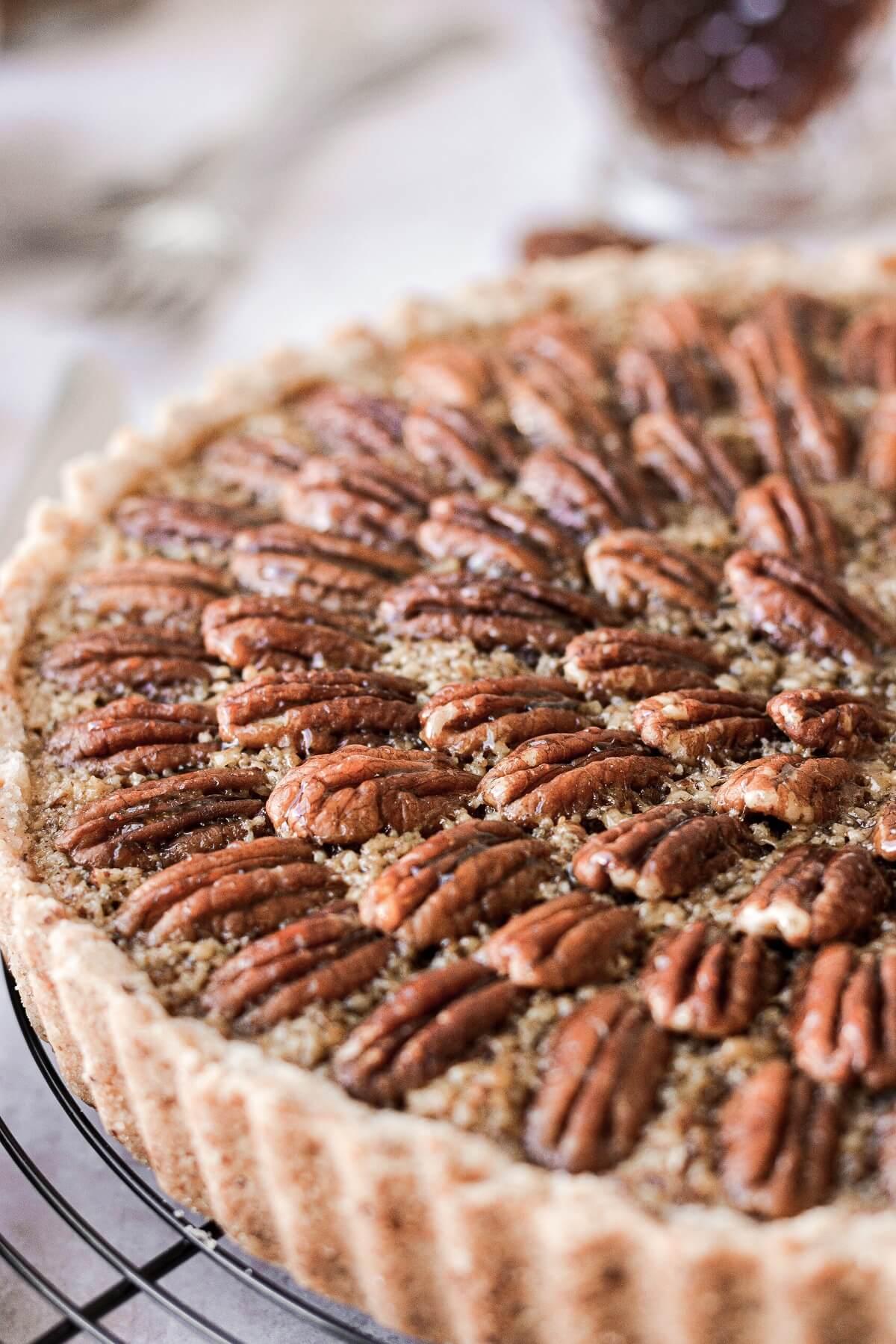 Closeup of pecans on top of a maple pecan tart.