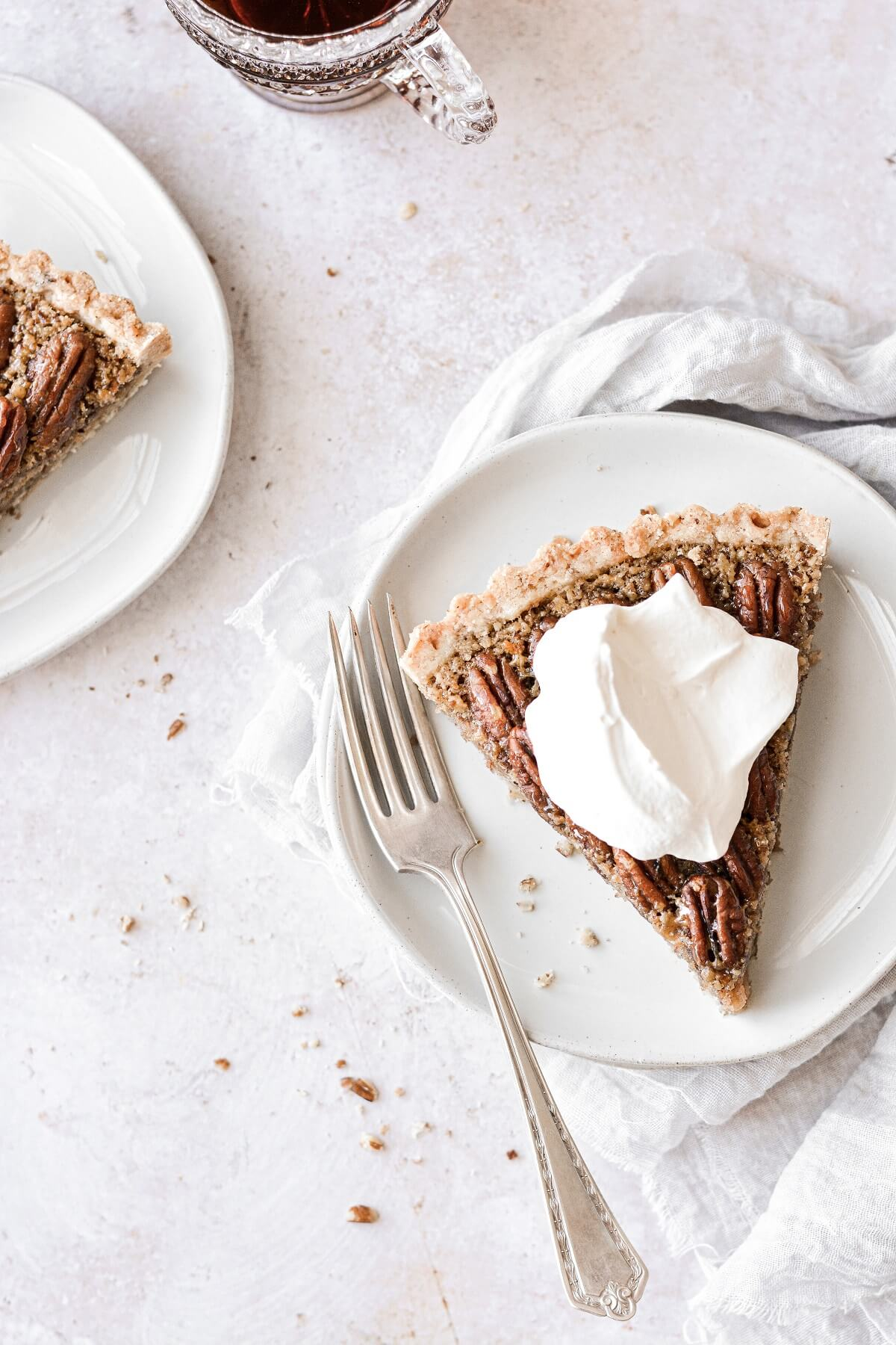 A slice of maple pecan tart topped with whipped cream.