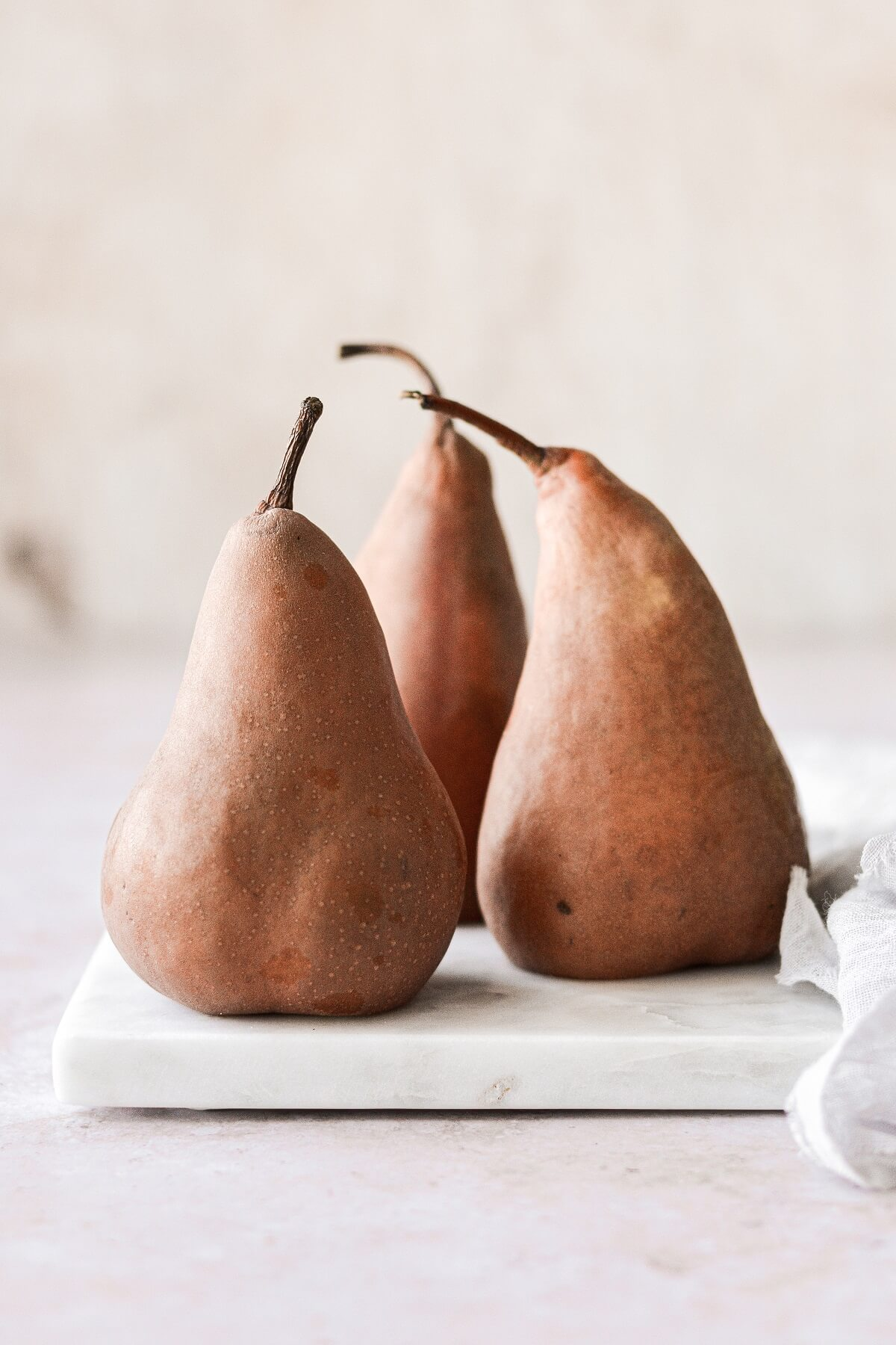 Three pears sitting on a white marble board.