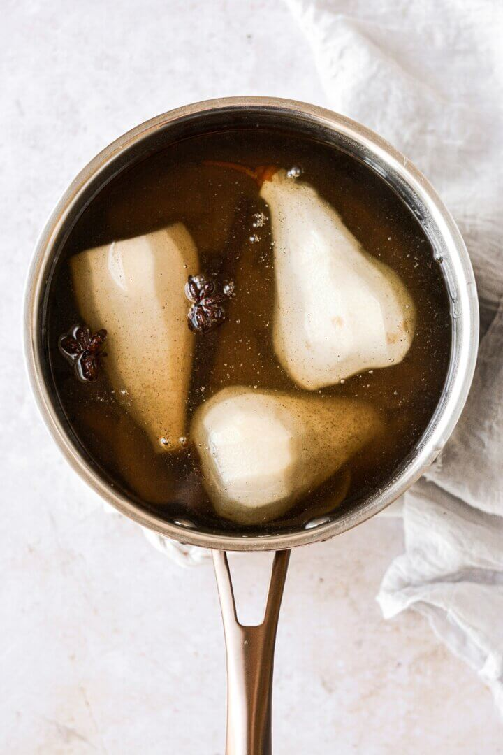 Poached pears and spiced syrup in a saucepan.