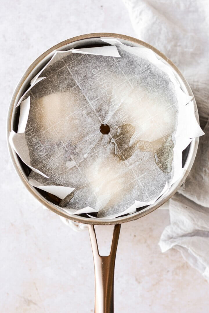 A saucepan of poached pears with parchment paper on top.