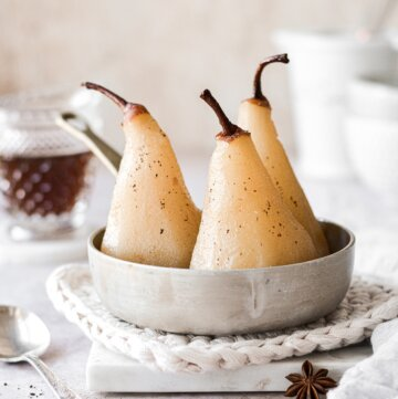 Three poached pears sitting in a pan of spiced syrup.