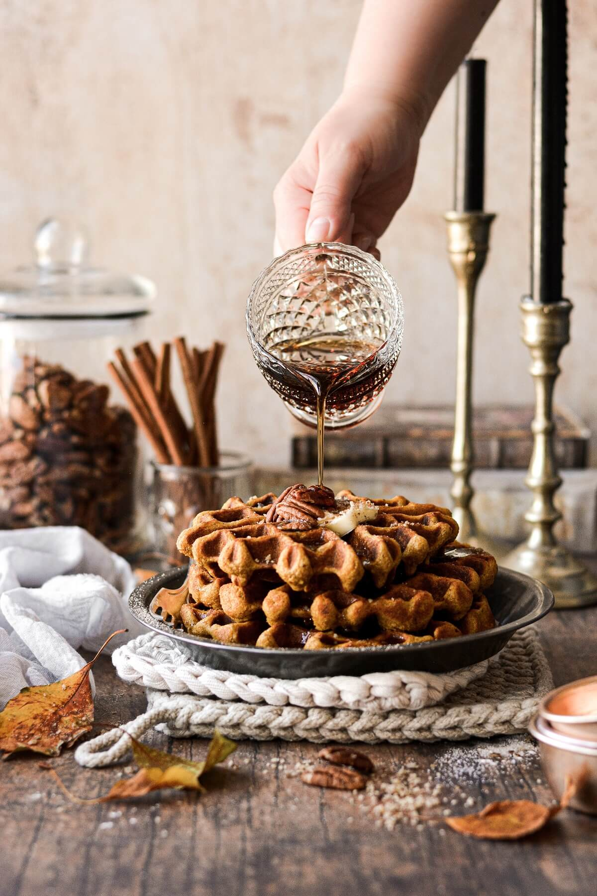 Maple syrup pouring from a glass pitcher onto a stack of pumpkin pecan waffles.