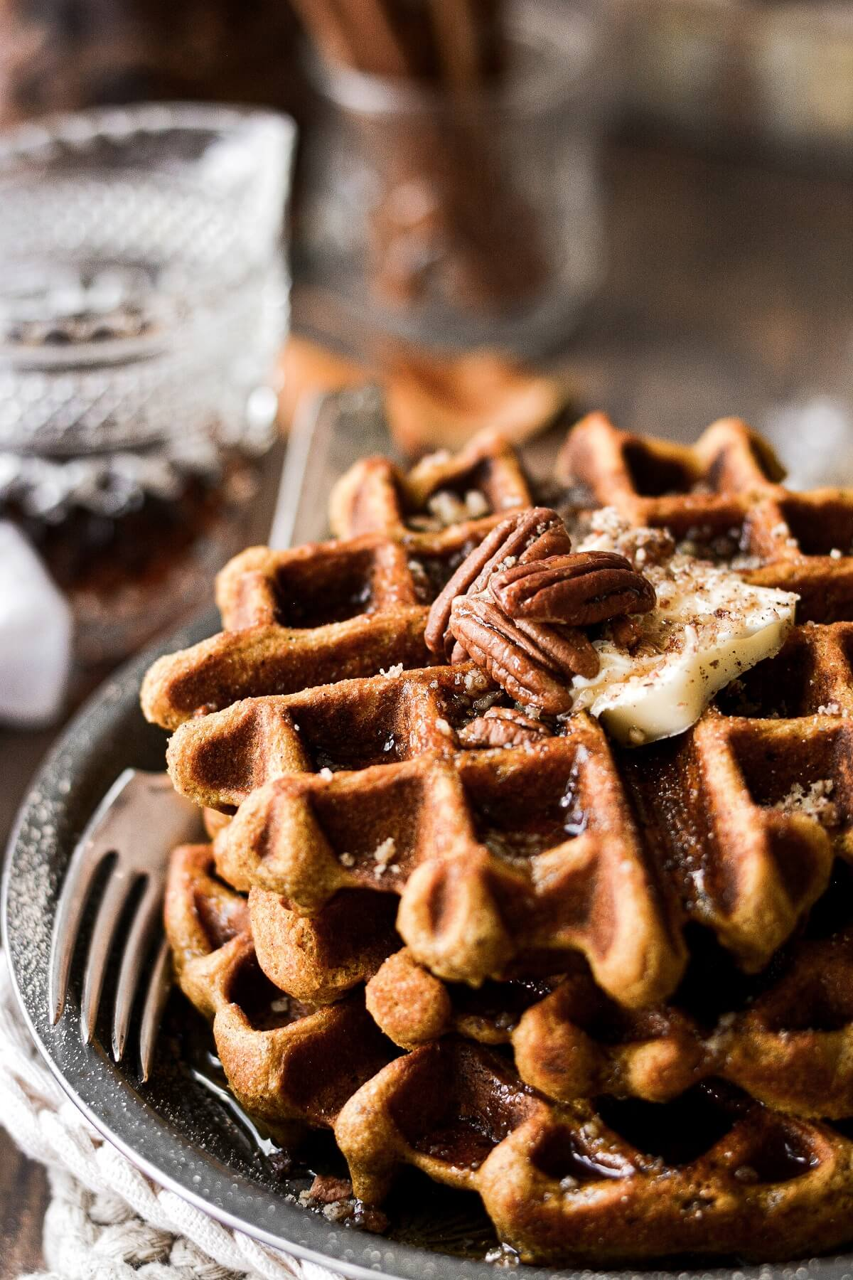 A stack of pumpkin pecan waffles topped with butter and pecans.