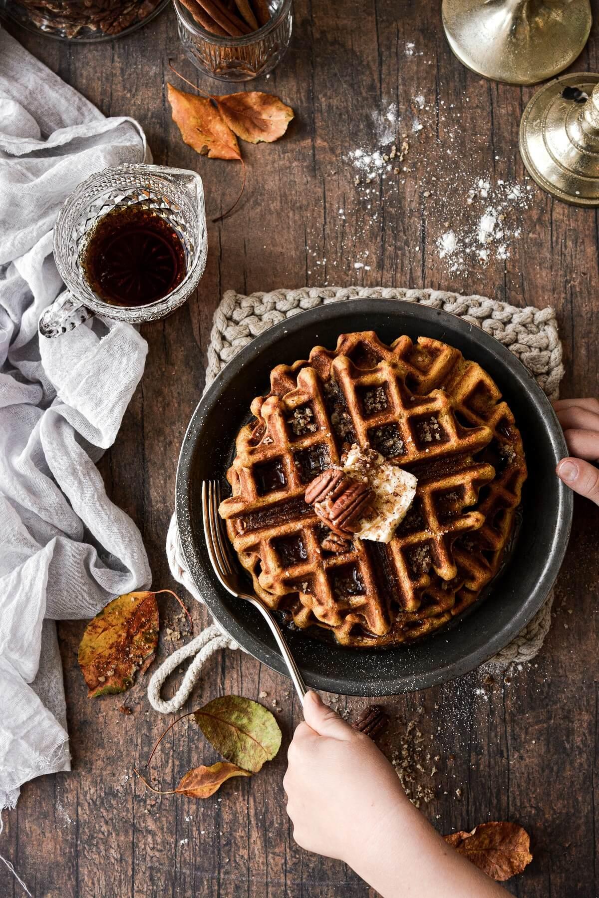 Hands reaching to cut into a plate of pumpkin pecan waffles.