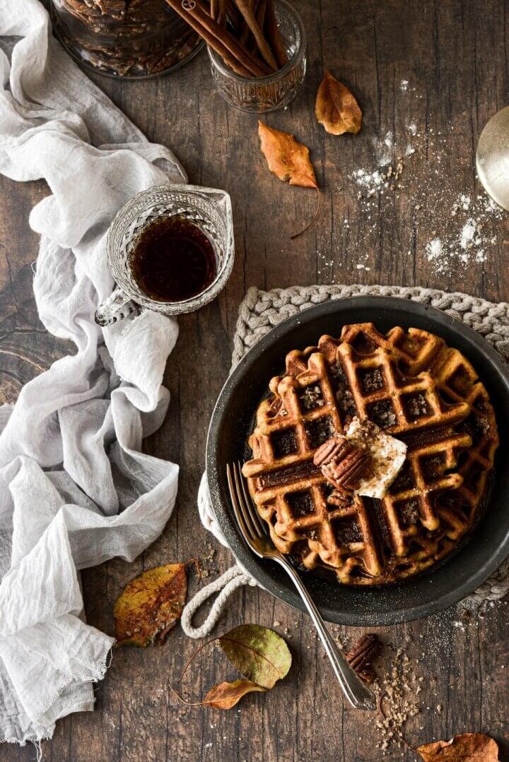 Pumpkin pecan waffles with a pitcher of syrup and leaves scattered around.