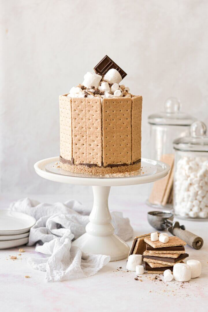 A s'mores ice cream cake on a white cake stand.