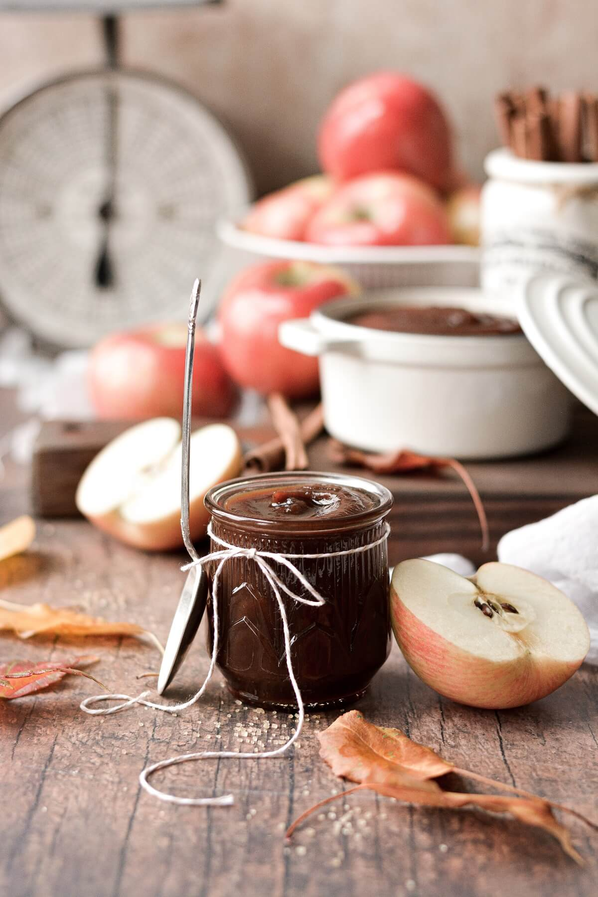 Apple butter in a glass jar, sourrounded by apples and leaves.
