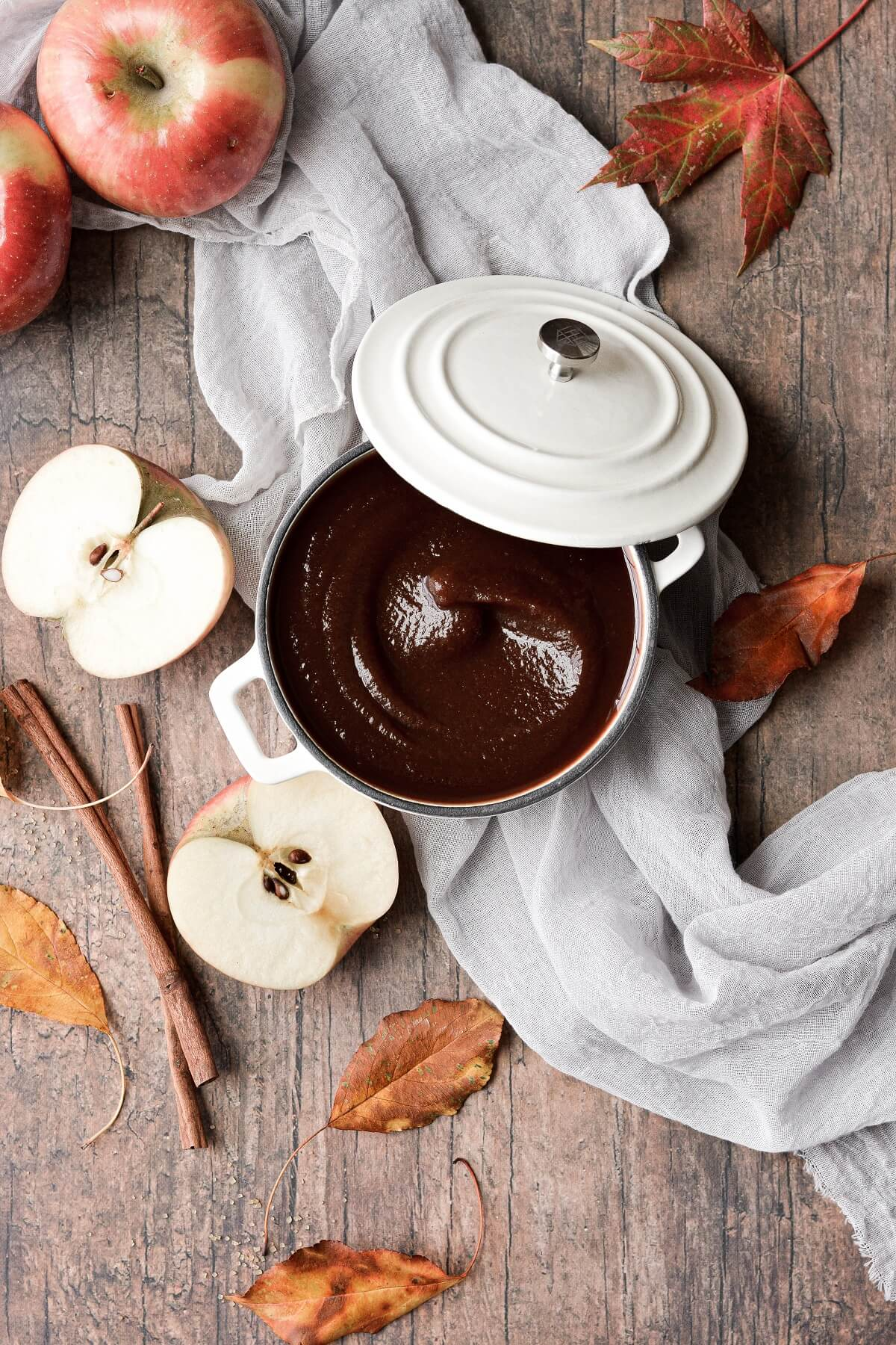 Apple butter in a white Dutch oven, surrounded by apples and leaves.